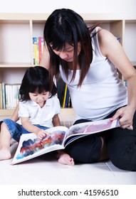 Pregnant mother and her daughter reading together.