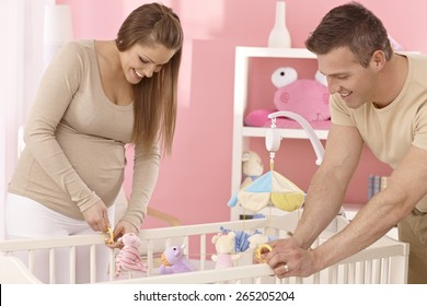Pregnant mother and husband preparing baby's cot, smiling.