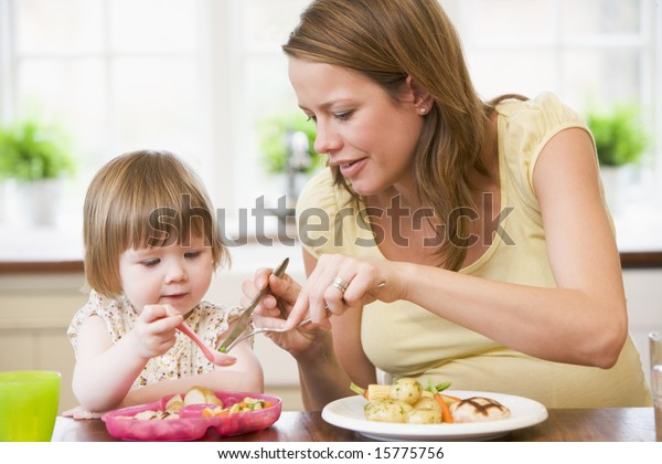 Pregnant mother in kitchen eating chicken and vegetables helping daughter eat