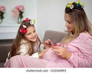 Pregnant mother painting nails her little daughter while wearing hair-rollers, at home
