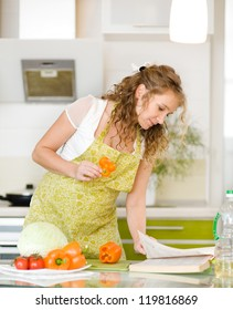 pregnant mother preparing food in kitchen and reading cooking recipe