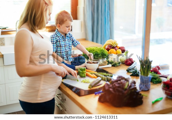 Pregnant mother and son preparing meal