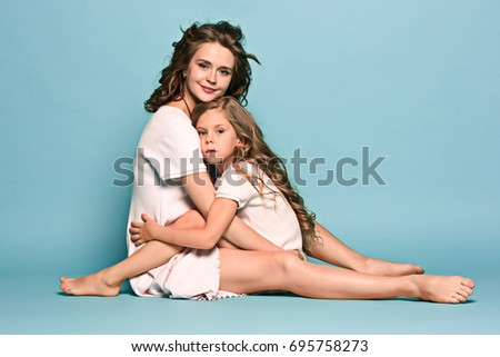 d6b1ef2b1d56 Pregnant mother with teen daughter. Family studio portrait over blue  background