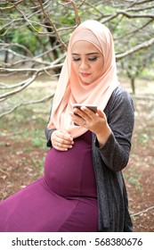 Pregnant muslim woman redaing somethin in her smartphone in the park