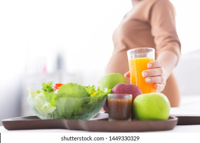 pregnant people drinking fresh orange juice and she use her hand holding glass, she feeling love and care her daughter, pregnancy health care promotion, she eating organic vegetable salad