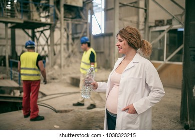 Pregnant scientist working woman drinking water in factory