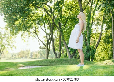 Pregnant smiling blond woman in white dress inhale fresh air in the park. Walk outdoor