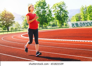 Pregnant sporty fitness woman jogging on red running track in stadium. Training summer outdoors on running track line with mountains on background. Sport, healthy lifestyle while pregnancy concept.