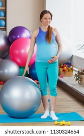 Pregnant sporty woman holds hand on the belly, soft focus background