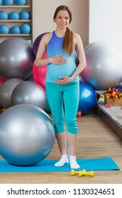 Pregnant sporty woman holds hands on the belly, soft focus background