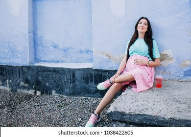 pregnant stylish girl in a pink skirt and a mint shirt is sitting on a step and holding on to the belly against a blue wall