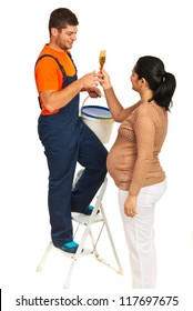 Pregnant wife giving paint brush to her husband to painting  their room isolated on white background
