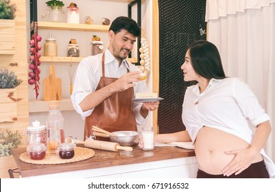 pregnant wife and husband cooking in the kitchen