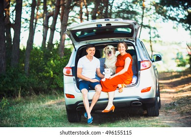 pregnant wife, husband and dog sitting in a car in the park