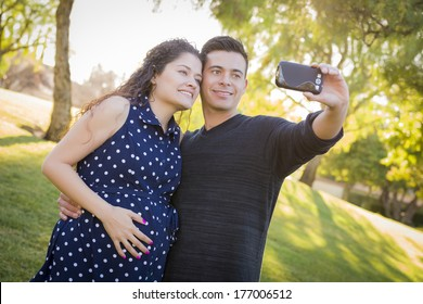Pregnant Wife and Husband Taking Cell Phone Picture of Themselves Outdoors At The Park.