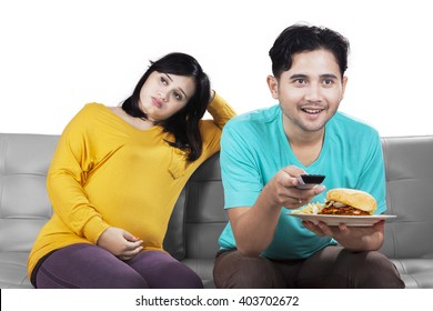 Pregnant woman angry because her husband watches TV, isolated on white background
