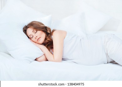 Pregnant woman asleep in bed