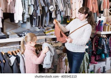 Pregnant woman with baby girl choosing clothes in a shop