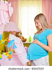 Pregnant woman in baby room