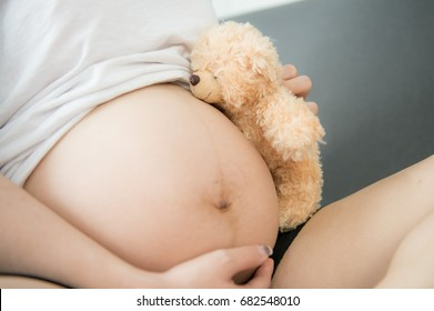 Pregnant woman with bear on her tummy, Pregnant mother showing her belly and holding a teddy bear,Cheerful happy nine month pregnant woman holding belly on white isolated background
