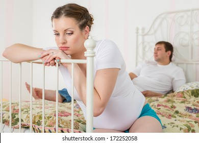 The pregnant woman becomes angry about the husband who lies on a bed and watches TV.