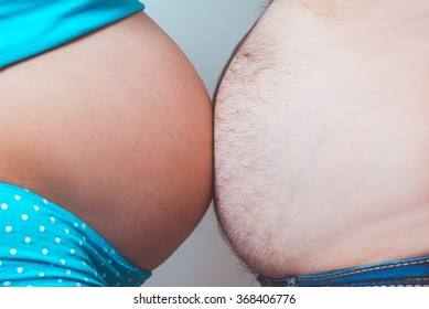 Pregnant woman belly touching the husband stomach