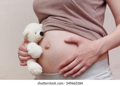 Pregnant woman belly with white teddy bear