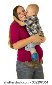 a pregnant woman with a big smile as she gets a kiss from her toddler boy.