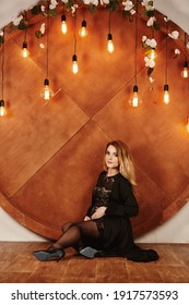 pregnant woman in black dress touching her belly on decoration wall with retro light bulbs. Motherhood, pregnant, people and expectation concept. Pregnant woman expecting baby. Maternity concept.