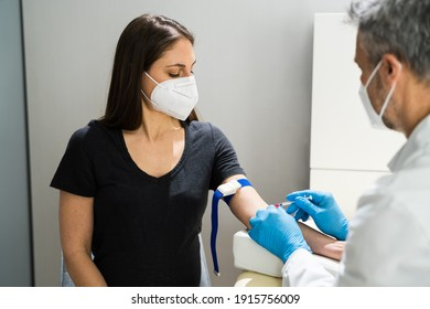 Pregnant Woman Blood Draw By Doctor In Laboratory In Face Mask