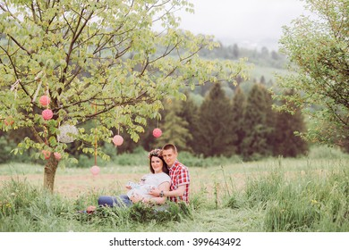 Pregnant woman in blue jeans and a T-shirt with her husband on the mountains background. Future parents