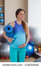 Pregnant woman with a bottle of water in the hand, soft focus background