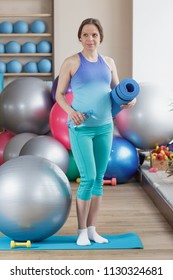 Pregnant woman with a bottle of water and mat in the hands, soft focus background