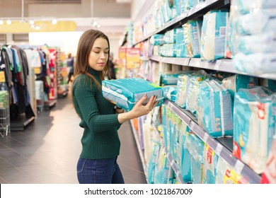 Pregnant woman buys diapers at the supermarket, portrait of young happy mother in shop mall