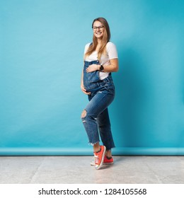 Pregnant woman caressing her belly over blue background. A cute young woman wearing glasses, and denim romper posing touching tummy communicating with her unborn child.
