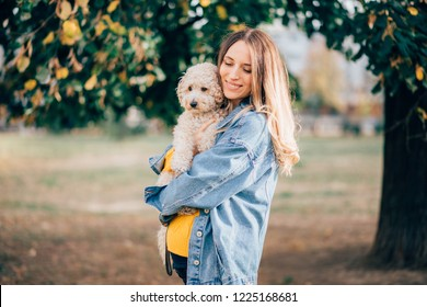Pregnant woman carrying dog in park