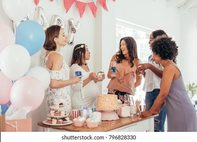Pregnant woman celebrating baby shower party with female friends at home. Group of multi-ethnic women at a baby shower.