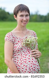 Pregnant woman with chamomile on the green meadow