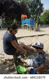 Pregnant woman and child playing with toys on sand at a playground on a sunny day on July 2017 in Poznan, Poland