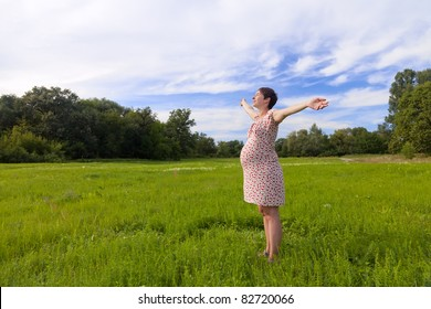 Pregnant woman with closed eyes on green meadow