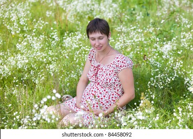 Pregnant woman with closed eyes sitting in chamomile background