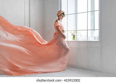 Pregnant woman dancing in pink evening dress flying on wind. Waving fabric, fashion shot