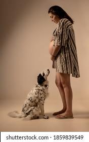 Schwangere mit einem Hund, der aussieht/wartet
