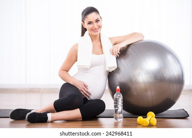 Pregnant woman is doing exercises with gymnastic ball.