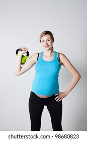 Pregnant woman doing exercises with kettlebell