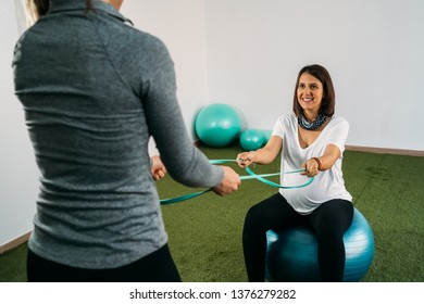 Pregnant woman doing fitness ball and pilates exercise with coach. Happy future mother preparing for childbirth.