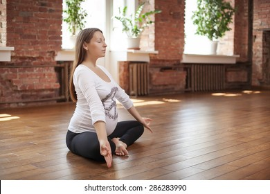 Pregnant woman doing yoga indoors.