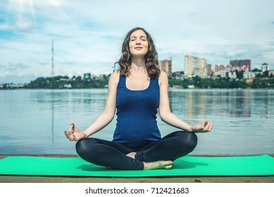 Pregnant woman doing yoga. Relaxation in the nature near the water