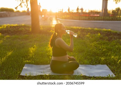 Pregnant woman drink water while sitting on yoga mat in summer park. Healthy lifestyle, expecting baby and child bearing concept.