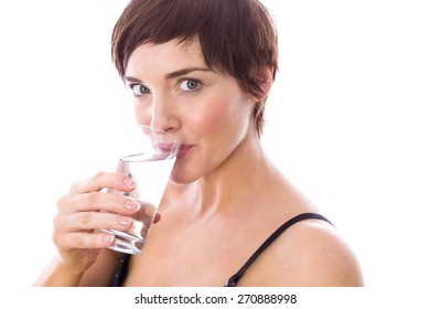 Pregnant woman drinking glass of water on white background